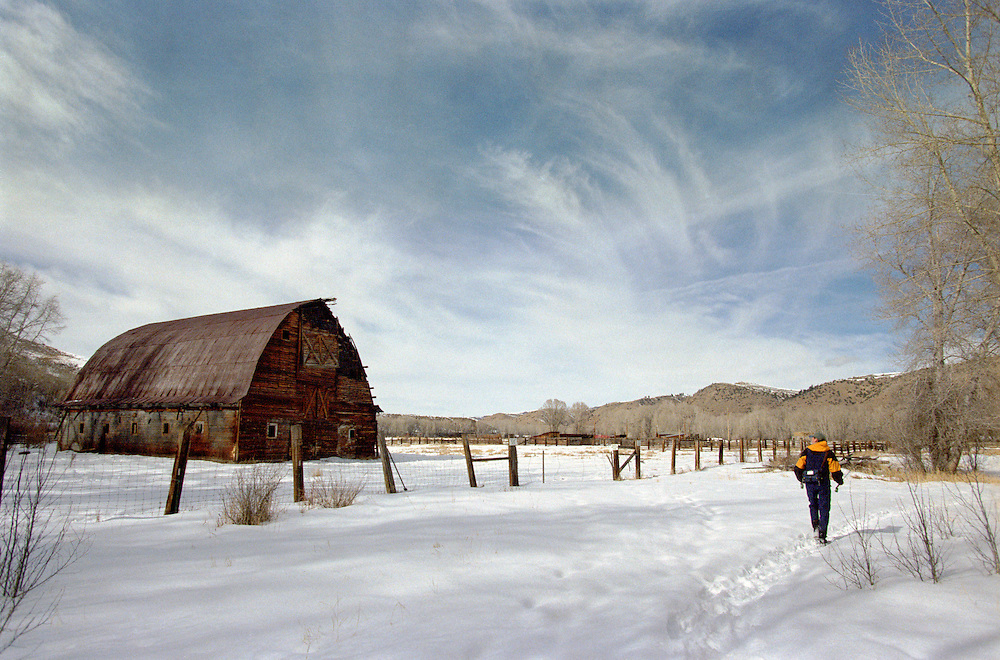 A fly fisherman hikes past an old barn for a day of Colorado fly fishing on a warm winter day