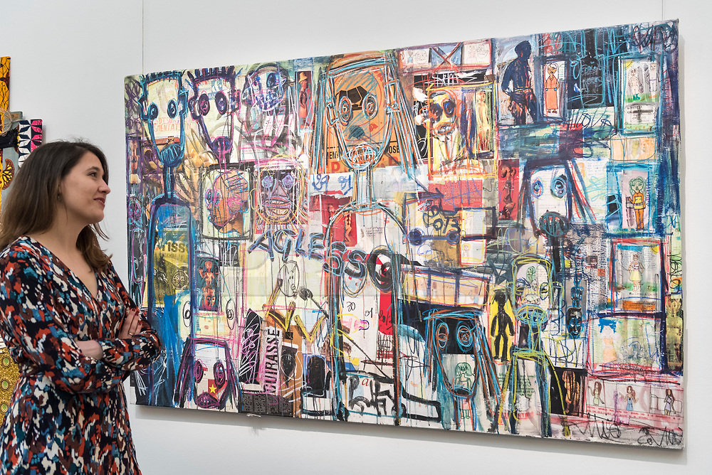 "© Licensed to London News Pictures. 29/03/2019. LONDON, UK. A staff member views ""Untitled"" by Abdoulaye Aboudia Diarrassouba (Est. GBP 8,000-12,000).  Preview of Sotheby's upcoming Modern and Contemporary African Art sale.  Works from artists across the African diaspora will be offered for sale on 2 April.  Photo credit: Stephen Chung/LNP"