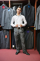 Portrait of young man posing with suits hanging in background