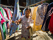 30 JULY 2016 - BANGKOK, THAILAND:  A woman hangs her laundry in the communal laundry area of the Pom Mahakan Fort slum. The community is known for fireworks, fighting cocks and bird cages. Mahakan Fort was built in 1783 during the reign of Siamese King Rama I. It was one of 14 fortresses designed to protect Bangkok from foreign invaders. Only of two are remaining, the others have been torn down. A community developed in the fort when people started building houses and moving into it during the reign of King Rama V (1868-1910). The land was expropriated by Bangkok city government in 1992, but the people living in the fort refused to move. In 2004 courts ruled against the residents and said the city could take the land. Eviction notices have been posted in the community and people given until April 30 to leave, but most residents have refused to move. Bangkok officials gave them a new deadline of September 1 but residents still refuse to move.      PHOTO BY JACK KURTZ