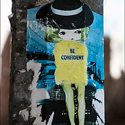 &quot;Be Confident&quot; urban graffiti Anime Girl sticker art  on side of street poll base  in Manhattan.<br /> <br /> Sticker art (also known as sticker bombing, sticker slapping, slap tagging, and sticker tagging) is a form of street art in which an image or message is publicly displayed using stickers. <br /> <br /> These stickers may promote a political agenda, comment on a policy or issue, or comprise a subcategory of graffiti.