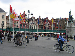 Bicyclists ride through The Markt, Market Place, main square, Bruges, West Flanders, Belgium