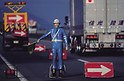"A Japanese battery-operated robot traffic officer, ""anzen taro"" (which means ""safety boy""), directs traffic at a construction zone on an expensive toll road near Mt. Fuji, outside Tokyo, Japan. (Man Eating Bugs page s 30, 31)"