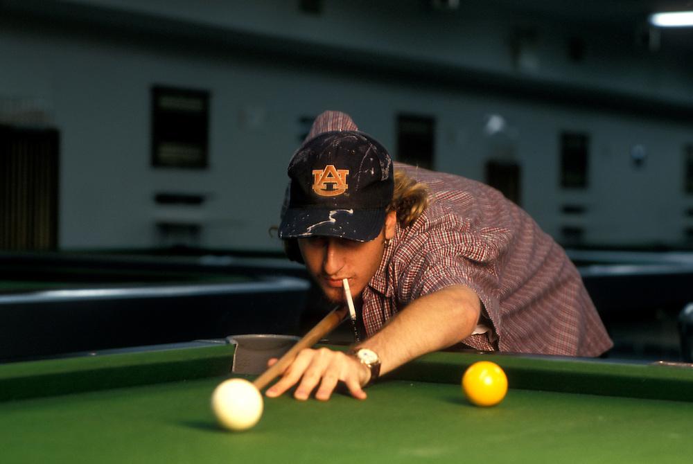 Canada, Manitoba, Winnipeg, (MR) Tim Jeffaries lines up shot while playing pool at Garry Billiards
