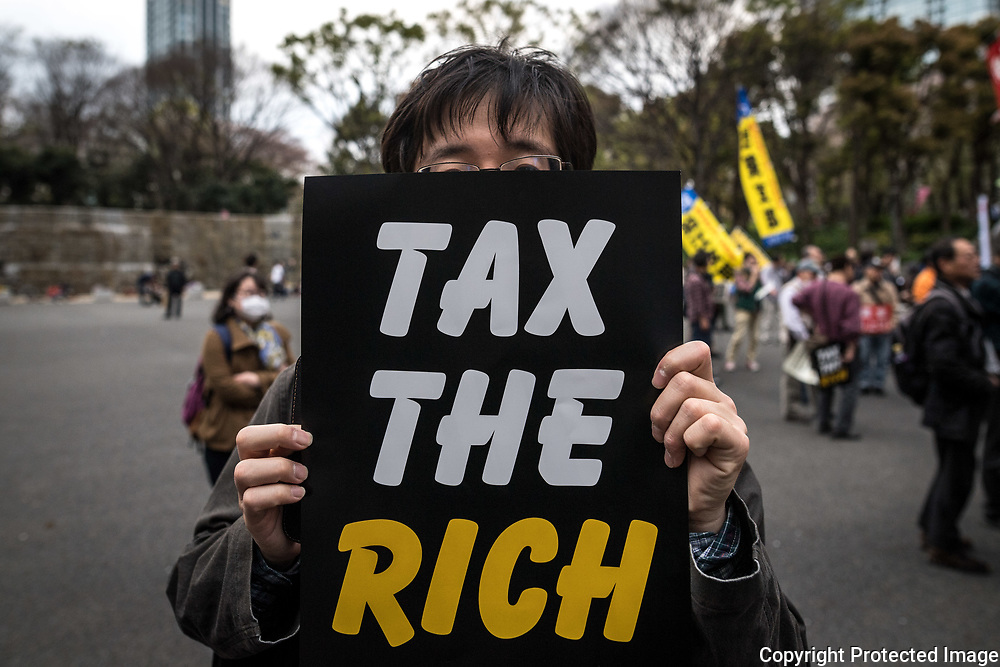 A protester holds a placard demanding a higher wage in Tokyo April 15, 2017, Japan. A Group of young people named Aequitas who means Equity in Latin, organised a demonstration to demanded a minimum hourly wage of 1,500 JPY (approx. USD 13.7), currently the minimum wage ranges from 700 to 900 JPY (approx. USD from 6,4 to 8,3). 15/04/2017-Tokyo, JAPAN