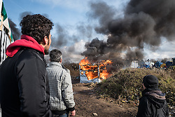 Licensed to London News Pictures. Calais, France. 03/03/16.  Refugees and volunteers watch as a shelter is razed to the ground by a fire. French authorities are clearing the southern half of the Calais 'Jungle' camp, which charities estimate to contain 3,500 people.. Photo credit : Rob Pinney/LNP