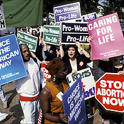 Pro-Life demonstrators march on Washington DC both sides of the Abortion Issue with people holding up signs: Stop Abortion Now, Pro-Woman, Pro-Life, Choice is the American Way