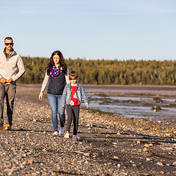 A couple and their daughter explore the Mowry Beach Preserve in Lubec, Maine.