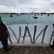 VENICE, ITALY - DECEMBER 18: Protesters hold a banner as they protest against large cruise ships in St Mark's basin on December 18, 2011 in Venice, Italy. Venetians and Environmentalists are opposed tocruise ships, which plough through the shallow Venetian lagoon, damaging the fragile buildings and canal banks.