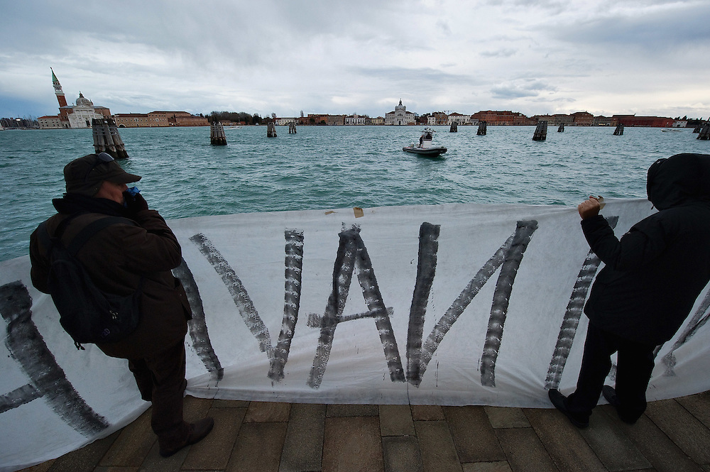 VENICE, ITALY - DECEMBER 18:  Protesters hold  a banner as they protest against large cruise ships in St Mark's basin on December 18, 2011 in Venice, Italy. Venetians and Environmentalists are opposed to cruise ships, which plough through the shallow Venetian lagoon, damaging the fragile buildings and canal banks.
