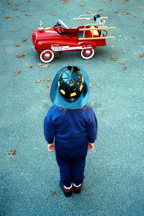 Young Boy, wearing fire helmet, standing in his driveway, admiring his fire truck. Model released.. .