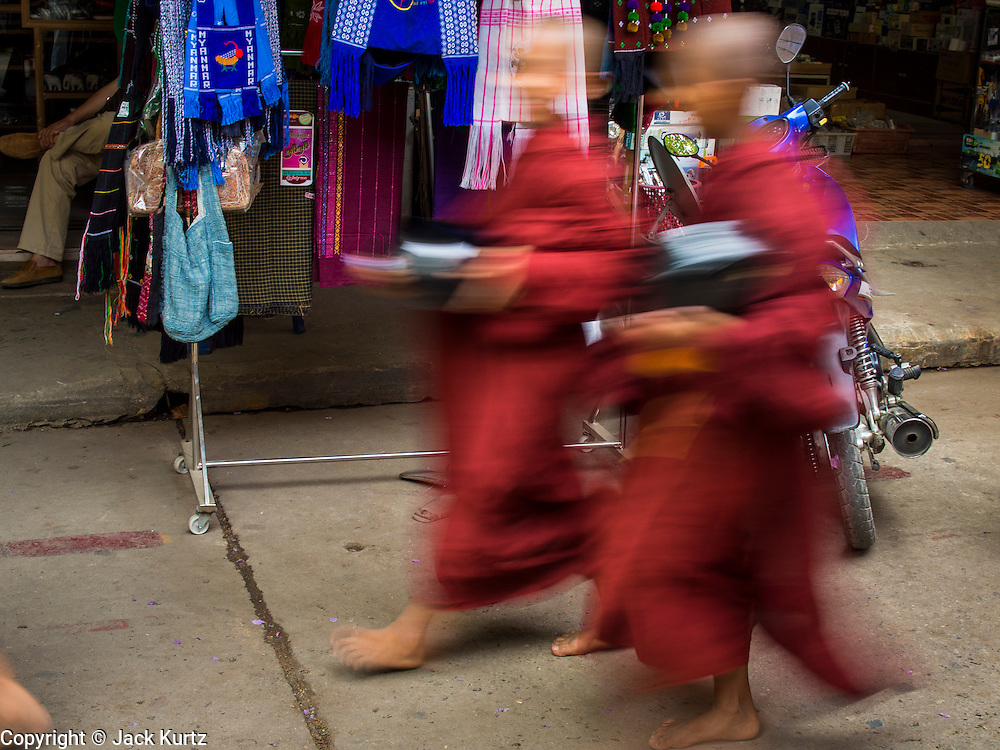 26 APRIL 2014 - TACHILEIK, SHAN STATE, MYANMAR: Buddhist monks and novices go out on their alms gathering rounds in Tachileik, Shan State, Myanmar (Burma). Most Burmese males become monks for at least a short period in their lives, sometimes more often than once. There are more than 500,000 monks and novices in Burma.   PHOTO BY JACK KURTZ