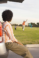 Woman Watching Husband and Child Fly Kite