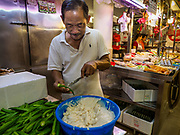 09 JULY 2017 - SINGAPORE: A vendor fills okra with fishmeal in the Tiong Bahru market. The popular Singapore treat can be fried or barbecued. Tiong Bahru market, in the midst of the Tiong Bahru Housing estate, was the first indoor market in Singapore and is considered one of the best markets in Singapore. It was built in 1955 in an effort to organize vendors and get them off the neighborhood streets. Tiong Bahru neighborhood is now one of the most popular neighborhoods in Singapore for both expats and Singaporeans.    PHOTO BY JACK KURTZ
