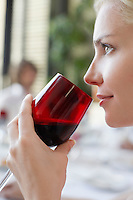 Young woman drinking from wineglass close-up profile