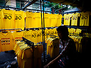 "03 JULY 2018 - BANGKOK, THAILAND: A man walks past a shop selling yellow tee shirts that say ""Long Live the King"" in Bobae Market. The birthday of King Maha Vajiralongkorn Bodindradebayavarangkun, Rama X, is 28 July. The King, the only son of Thailand's late King Bhumibol Adulyadej, became the King of Thailand in 2016 after the death of his father. King Vajiralongkorn was born on 28 July 1952, a Monday. In Thai culture each day of the week has a color, and yellow is the color is associated with Monday, so people wear yellow for the month before his birthday to honor His Majesty.   PHOTO BY JACK KURTZ"