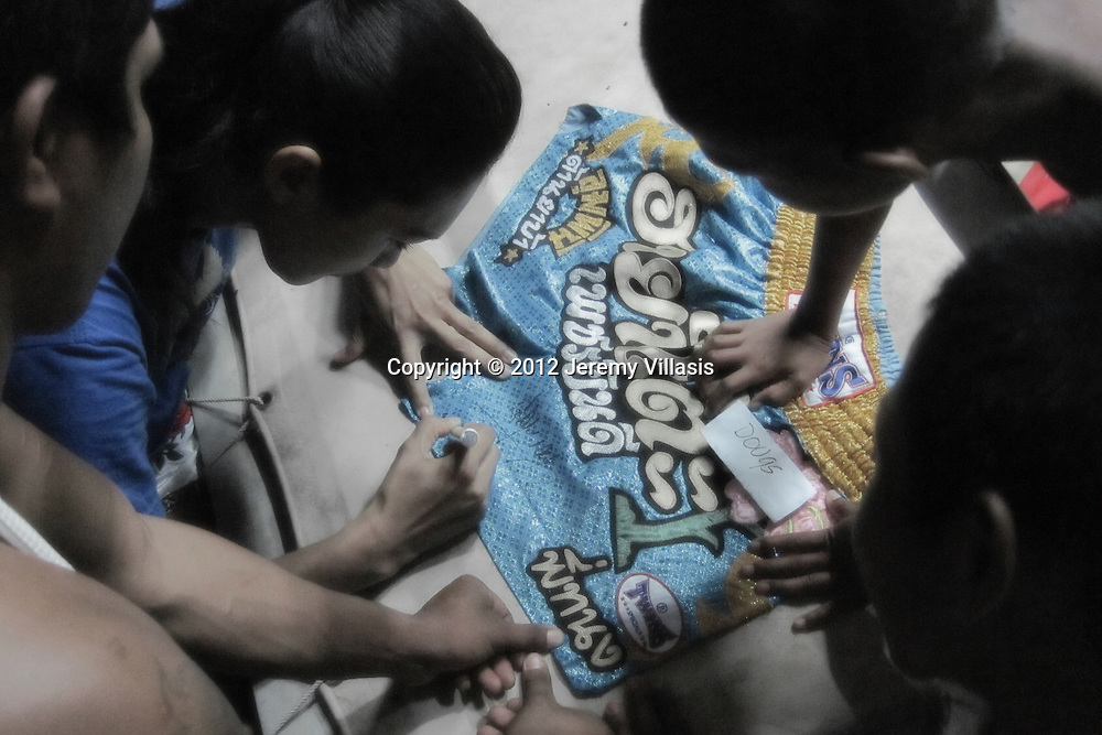 Nong Toom signs a boxing shorts for a fan after a training session.