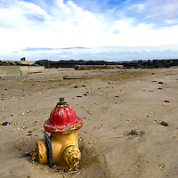 A fire hydrant is nearly buried in the sand beside debris in Atlantic City, NJ February 8, 2016.
