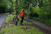 A father and son walk across a verge in woods south of Sheffield, England UK.
