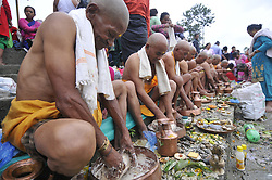 August 21, 2017 - Kathmandu, Nepal - Nepalese Devotees perform religious ritual after a holy bath on the banks of the Bagmati River during the celebration of Kuse Aunsi or Father's Day at Gokarna Temple in Kathmandu, Nepal. On the day of the new moon, families also pay their respects to their deceased fathers. (Credit Image: © Narayan Maharjan/NurPhoto via ZUMA Press)