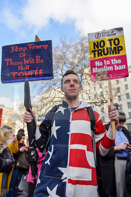 © Licensed to London News Pictures. 04/02/2017. London, UK. A man carries signs, joining thousands of people, standing against racism and Islamophobia, in Whitehall outside Downing Street to oppose the travel ban on Muslims, from seven countries, imposed by Donald Trump, U.S. President. Photo credit : Stephen Chung/LNP