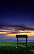 A lonely beach bench at dusk on Perth's City Beach