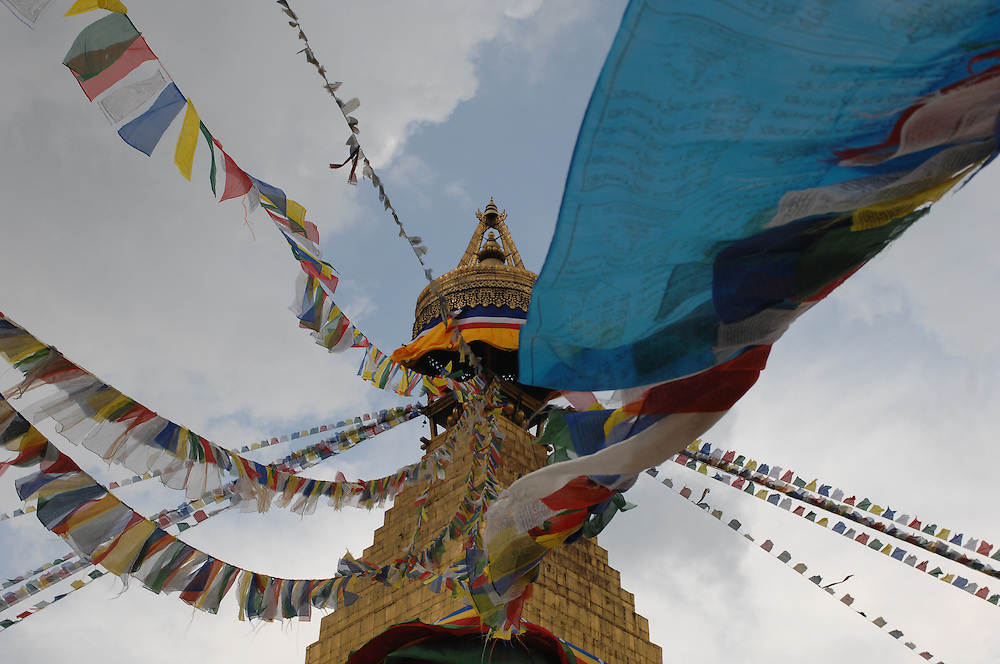 Prayer flags whipping in the wind at Boudhanath stupa, in Nepal.