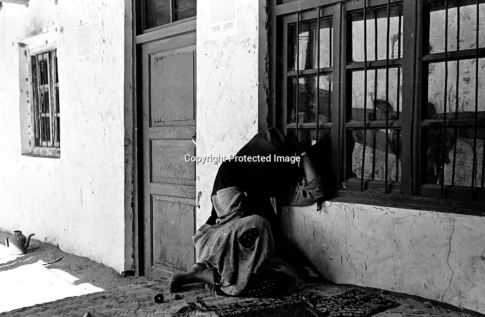 HOTAN,  OCTOBER 31: an old pilgrim woman sitting inside the courtyard of a mosque in the Taklamakan desert.The woman gave up her property after her husband died and settled in the mosque.n.UighurUighur muslims in China's western Xinjiang province mostly stick to islamic lifestyles due to their proximity to Afghanistan & Pakistan .Uighur muslims in southern Xinjiang province lead very basic lifestyles and have an average monthly income of about 50 US$..Today, 47 percent of Xinjiang is Uighur and 41 percent is Han. Smaller groups of other Turkic Muslims, including Kyrgyz, Kazakhs, Tajiks and Uzbeks, make up the remainder of the population ..The government maintains tight control over Uighur culture.All mosques are required to register with the government. In 2001, authorities called in 8,000 imams for special training on the Communist Party's ethnic and religious policies. In 2002, Xinjiang's top university eliminated all instruction in the Uighur language. .