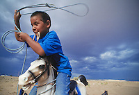 Seven year-old Lance Boyd  practices roping from the back of his rocking horse.