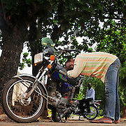 12-05-29   - LOME, TOGO -    Zemidjan ('take me quickly' in  Fon) driver Spero Deguenon demonstrates how he sleeps on his motorcycle in Lomé, Togo on May 29. Underpaid, rarely thanked and working all hours to make a meagre living, they find very few moments of calm and quiet in their lives. And so, the moto-taxi men have perfected various ways of calmly sleeping on their motorbike as they wait for  their next customer. And so, on the move amidst the chaos and bustle of daily life, they relax and sleep.  Photo by Daniel Hayduk