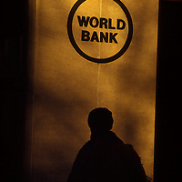 A silhouetted person beneath a sign on a wall of the old World Bank Headquarters building in Washington, DC.