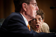 Former White House Budget Director ALICE RIVLIN makes a comment to former Senate Budget Committee Chairman Senator PETE DOMENICI (R-NM) as they testify before a Senate Finance Committee hearing on Capitol Hill Tuesday about the looming fiscal crisis.