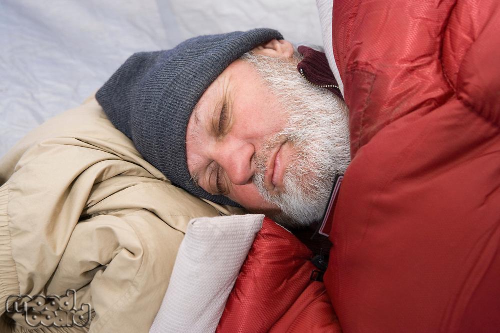 Senior man sleeping in a tent