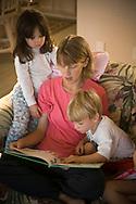 Mother reading a book to enthralled children at Topsail Beach, North Carolina. (releasecode: jk_mr1001, jk_mr1002, jk_mr1003) (Model Released)
