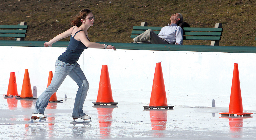 (021109  Boston,  MA)  Alexandra Abuhoff, 18, of Boston, skates around a patch of slushy ice as a man suns himself at the Frog Pond on the Boston Common, Wednesday,  February 11, 2009.   Staff photo by Angela Rowlings.