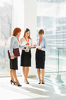 Full-length of businesswomen discussing over documents in office