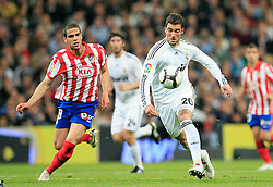 MADRID, SPAIN - Sunday, March 28, 2010: Real Madrid Club de Futbol's Gonzalo Higuain and Club Atletico de Madrid's Jose Manuel Jurado during the La Liga Primera Division Madrid Derby match at the Estadio Santiago Bernabeu. (Pic by Hoch Zwei/Sprimont Press/Propaganda)