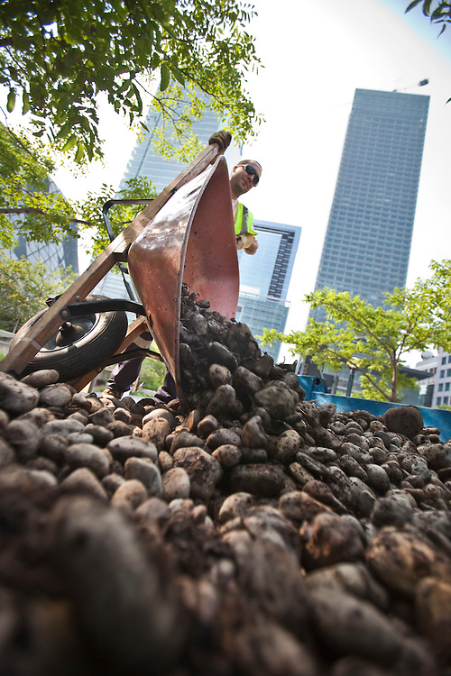 City of Toronto workers  clear rocks from gardens in a park close to the security zone around the G20 site, June 25, 2010.<br /> AFP/GEOFF ROBINS/STR