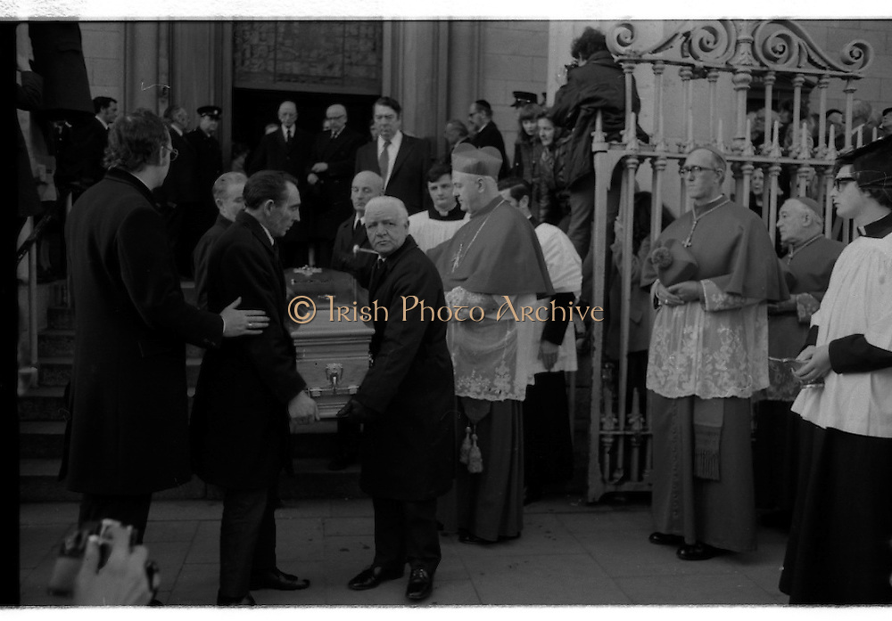 Funeral of Sinead Bean DeValera.    (H82)..1975..09.01.1975..01.09.1975..9th January 1975..Today saw the funeral of Sinead Bean DeValera take place at the Pro Cathedral, Dublin. She was the wife of Ex-President Eamon DeValera. Mrs Devalera was a noted author of childrens literature..Mrs DeValera, Born 3rd June 1878. Died 7th Jan 1975...Image of Cardinal Conway,Archbishop of Armagh and Primate of All-Ireland blesses the coffin containing the mortal remains of Sinead Bean DeValera as leaves the Pro-Cathedral. The burial would take place in the family plot in Glasnevin Cemetery