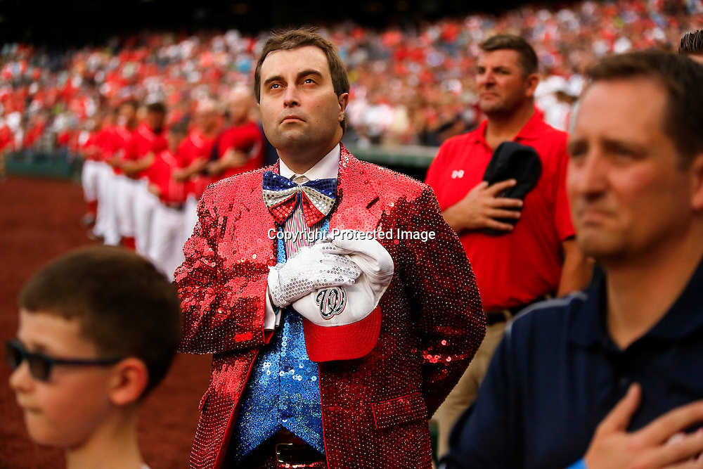 Washington Nationals season ticket holder Tripp Whitbeck wears a sequined suit and bow tie during the national anthem on the field before an 11-0 Nationals win over the Philadelphia Phillies at Nationals Park. Whitbeck was one of the nine fans on fan appreciation night who were able to be on the field before the game to greet the players as they took their positions for the first pitch.