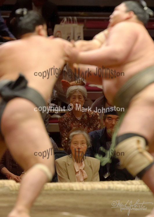 """Two attentive fans watch the action at the Tokyo Spring """"basho"""" at Kokugikan."""