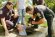 Miles Naylor hands a small puppy out to Decatur Police sergeant Jimmy Hood while officer Chuck Zanda (left) watches.  The puppy was stuck in a pipe underneath 12th Ave NW at 4th St.  A person walking on the sidewalk heard the puppy's yelps and called animal control and Decatur PD.  Decatur Fire Ladder 2 was eventually called in to flow water into the drain pipe to coax the scared puppy to come to Naylor who nabbed him and pulled him out.  The puppy appeared to by a lab mix.  Naylor, an animal cruelty investigator, said that he is required to keep the puppy seven days before he is eligible for adoption.  Everyone at the scene from rescuer to bystanders expressed a desire to have the puppy so he will have no shortage of places to live.  photo by Gary Cosby Jr.  9/30/06