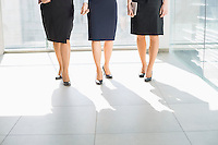 Low section of businesswomen standing on tiled floor in office