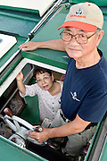 """Kenichi and Etsuko Yasuda, president and manager of """"yakata-bune"""" pleasure boat operator Harumiya Co., pose for a photo aboard one of their five-strong fleet of boats near the company headquarters in Tokyo, Japan on 30 August  2010. Photographer: Robert Gilhooly"""