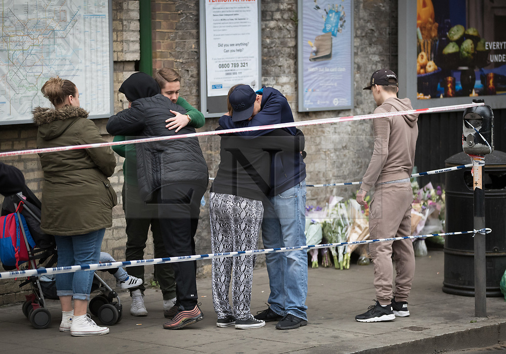 © Licensed to London News Pictures. 17/10/2017. London, UK. People believed to be friends and relatives of the victim console each other after placing floral tributes near the crime scene. Police are investigating after a man in his 20's was stabbed to death and two others were injured in an incident on Monday night outside Parsons Green underground station a terrorist attack took place last month. Photo credit: Peter Macdiarmid/LNP
