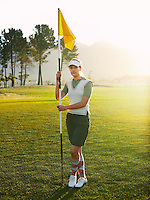Young female golfer holding flag portrait
