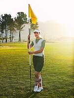 Young female golfer holding flag portrait