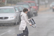 A woman walks across the street as snow falls in Oxford, Miss. on Sunday, March 21, 2010.