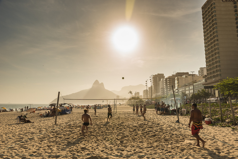People playing a game of soccer volley on the beach op Ipanema at sunset, Rio de Janeiro, Brazil.