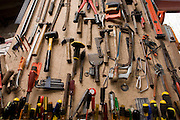 A collection of domestic tools stored on the wall of a small farmstead garage.